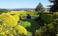 Keyhole shaped lawn at Ascott House Gardens, Buckinghamshire, UK, highlights the view past the Venus fountain towards the Chiltern Hills.