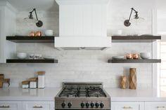 Modern Farmhouse interior design by Lindye Galloway Design. White kitchen, white shaker cabinets, white marble backsplash, open shelving, brass hardware, and swing arm sconce with kitchen shelf styling.