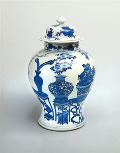 A blue and white vase and cover Qing dynasty, 19th century of baluster form, the sides painted in bright cobalt blue with a group of precious objects comprising jardinieres with flowering and fruiting plants on ornamental rockwork, tables and stands, the domed cover with fruits and flowers 43 cm high