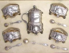 Exquisite antique 19th century French sterling silver condiment set, comprising of four open salt cellars and one lidded mustard pot, each ornately decorated in Louis XVI styling and bearing a lavish medallion cartouche surrounded by flowers and monogrammed with engraved initials CD or CO. Has gilt vermeil interiors. The set retains the original salt spoons and mustard spoon, also embellished at the handle with a classical floral decoration. The back of the salt spoons have a scalloped shell…