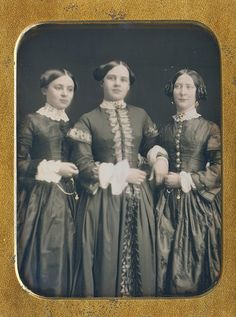 I can't decide whether that is mother on the right, or an older sibling. She is the only one wearing earrings, but wouldn't mother be in the center? Maybe, she is an auntie indulging her nieces with a picture. In any case, her features are very different. They are all very attractive and their dresses are grand.