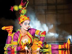 A feamle performer dresses as a clown with legs extended and arms at 90-degree angles at Cirque duSoleil - La Nouba