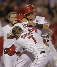 Los Angeles Angels' Kole Calhoun, from top, Chris Iannetta and Andrew Romine celebrate their win against the Seattle Mariners during the 11th inning of a baseball game in Anaheim, Calif., Friday, Sept. 20, 2013. (AP Photo/Chris Carlson)