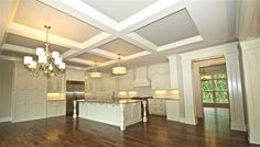 Complete custom kitchen design by Arrow Millwork and Cabinetry, Greendale, WI. Huge dream kitchen, unique ceiling beams, white cabinetry, large island with sink and storage, chandelier lighting, bold pillar entry moulding