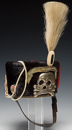 """returnofcowboyprince:  LATE MODEL HUSSAR BUSBY (PELZMUTZE)  black bearskin fur body with silver skull and bones planchet. Brass """"ribbon""""-style banner. Complete with cream colored plume and red cotton hat overlay."""