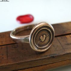 Wax seal ring with a tiny heart pierced with an arrow, a pierced heart, the symbol of Love.  The ring was made using an impression of an antique wax seal.  The wax seal used in creating this ring dates back to the 19th Century, an antique wax seal from England.  Note: * ring made of solid bronze * this ring style adjusts from size 6.5 - 9 * the band width is 3mm * size of wax seal design is about 12mm across * no frills - shipped with no meaning card, no gift packaging * the ring you will…