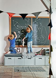 Children drawing on a chalkboard standing on a vtwonen storage bench in a…
