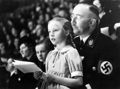 Chief of the German Police and Minister of the Interior Heinrich Himmler with his daughter Gudrun on his lap watch an indoor sports display in Berlin (March 6, 1938). After the allied victory, she was arrested and made to testify at the Nuremberg trials. Having never renounced Nazi ideology, she has consistently fought to defend her father's reputation, and has become closely involved in neo-Nazi groups that give support to ex-members of the SS. She married Wulf Dieter Burwitz, an official…