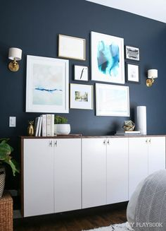 Dark navy walls, white floating credenza, and gallery wall above. Love this bedroom home decor look!