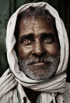 Portrait of a brown skinned man with a grey beard and a calm, welcoming look in his eyes.
