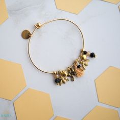 Honey is a charm bangle inspired by the humble bumble bee that reminds us of the importance of hard work, to extract the honey from life, and to achieve the impossible. The bangle features brass bumble bees and a 22k gold plated jasmine flower charm on a 22K gold plated open-close bangle.
