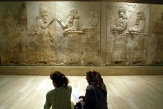 Two Iraqi women talk in front of Assyrian mural sculptures July 3, 2003 as the Baghdad museum briefly re-opened to display ancient Nimrud treasures. One of the most significant archaeological finds of the 20th century, the Nimrud treasures were destroyed by Islamic State militants, the Iraqi ministry announced 5 March 2015. Photo by Radu Sigheti/Reuters