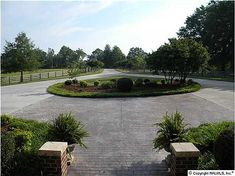 FRAMED WITH A LONG CIRCULAR DRIVEWAY, FENCING & LUSH LANDSCAPING
