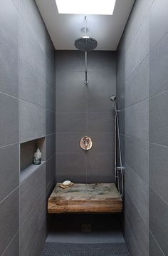 Love the weathered wood bench seat with the sleek gray tiled shower.  Gives warmth and texture.