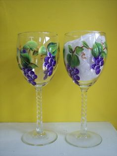 2 wine glasses 7 3/4 in. high---10 oz.  Two Twisted Stem Glasses for $ 16.00  Grapes, Grapes, and more Grapes. This twisted stem wine glass is covered with purple grapes, vines and leaves. The colors in the photos do not show the vivid, true purple of the grapes. Each is individually hand painted with a baked on finish for lasting beauty. The colors remain vivid and clear even after years of hand washing.  My husband and I design and do all of our own hand painting.