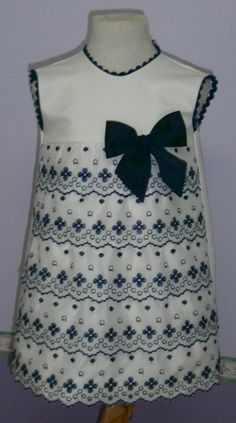 Vestido para bebe niña en nido de abeja beige adornado con tirabordada y piquillo en azul marino.