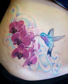 Beautiful humming bird with flowers tattoo. I love that it doesn't have allot if black outline.