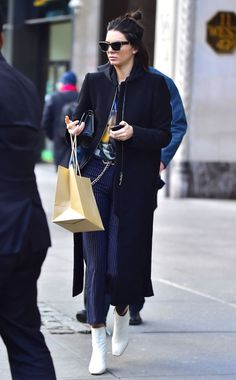 In a graphic tee, black coat, Miaou cropped pinstriped trousers, white ankle boots andBalenciaga Eyewear while out shopping in New York.