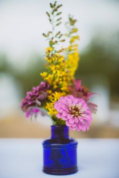 blue cobalt vase with florals is such an easy idea for your table decor. See more of this farm wedding here http://www.weddingchicks.com/2013/12/05/diy-wildflower-wedding/