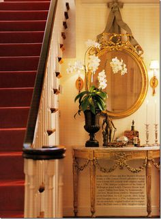 Decorating with Tea Caddies~ A tortoise shell caddy, gilt mirror, sconces, carved demilune table and white orchid in an urn - Jane Moore, 2000 Veranda Magazine