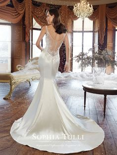 Sophia Tolli | Style No. › Y21510 | A simple silhouette with decadent details, lustrous satin slim fit and flare gown Bobbi offers the fashion savvy bride many moments of joy. Hand-beading highlights a gorgeously scooped neckline and shoulder straps while lace appliqués frame the bodice and stunning plunging illusion back neckline. A back zipper trimmed with diamante buttons and a chapel length [...]