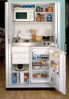 The doors of this mini kitchen are perfect. It would be such a space saver to have them pull out and then fold over the inside of the cabinet