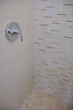 Shower includes porcelain and glass tile mosaic on the walls and a stone blend on the floor.