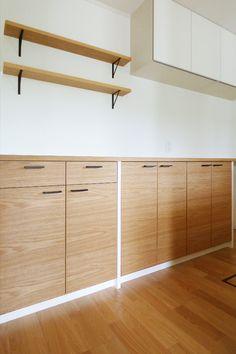 北欧風のキッチン背面収納。今回はナラの突板と白い化粧板の組み合わせによるデザインをご提案させていただきました。ナラ材のみを使用したデザインになると重厚感や木の質感は強く感じられるのですが、その一方で設置する空間との兼ね合いによっては少し強い印象を生みすぎてしまう場合もあります。今回のお客様の場合ですとご自宅の新築にあわせてのオーダーでしたので床材の色味や空間の雰囲気を事前に調査させて頂き、比較的明るい雰囲気の空間となっておりましたのでディスカッションを重ねた上で最終的に白と木質の組み合わせによる軽快な印象を与えられるデザインに決定致しました。キッチンエリアで使用する家具という事もあり天板のトップ面も化粧板で仕上げており水に強くメンテナンスのし易さ等も考慮した提案となっています。また今回も取手や棚板のブラケットなどは特注で制作しており複数の素材がうまくマッチした仕上がりとなりました。