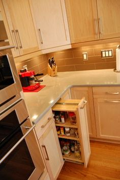 This contemporary kitchen features double stacked natural maple shaker door  cabinets and two toned quartz countertops