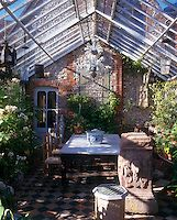 A conservatory extension is filled with plants and is used as a dining room