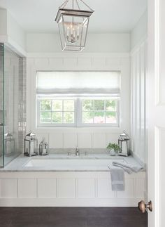 The perfect place to relax, this stunning cottage bathroom boasts a wainscoted drop in bathtub accented with a marble deck a polished nickel tub filler fixed in front of a board and batten wall framing a window dressed in a white linen shade lit by a Smal Built In Bathtub, Drop In Bathtub, Bathtub Drain, Tile Around Bathtub, Sunken Bathtub, Outdoor Bathtub, Bathtub Tile, Shower Tiles, Bedrooms