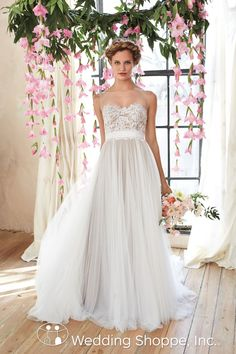 A whimsical lace and tulle wedding dress. The illusion neckline gives the feel of a strapless dress.
