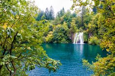 waterfall splashes into blue waters in Plitvice Lakes National Park, Croatia