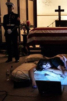 """Todd Heisler won the Pulitzer Prize for this photo where, on the night before the burial of her husband, Katherine Cathey asked to sleep next to his body for the last time. The Marines made a bed for her and one of the Marines asked if she wanted them to continue standing watch as she slept. """"I think that's what he would have wanted"""" she said."""