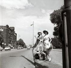 Liften. Twee vrouwen met hoed en bagage staan te liften langs een straat te Den Haag, Nederland 1964.