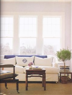 Understated traditional living room with beautiful windows and just a touch of blue. Great monogram on the pillow too!