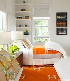Sally Markham, shelves and art by window. pop of orange