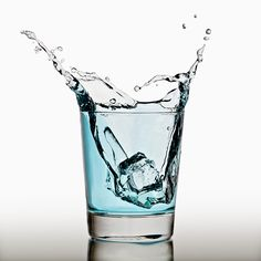 Ice cube splashing in a cool glass of water