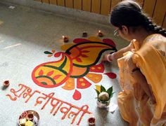 In this photo we can see a woman painting a Rangoli pattern