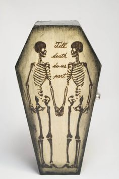 """This small wooden coffin can be used as a jewelry box or the ring holders can be removed for the entire space to be useable. It is lined with soft red felt and trimmed with real black leather. The outside has been stained ashy and black with a burning of two skeletons and """"Til death do us part"""" on the top of the coffin. It has also been treated with polyurethane to protect the color and design and give it a glossy look and feel.   Size: 5"""" x 3"""" x 1.5"""" and inside: 4.2"""" x 2"""" x 1""""  Jewelry is…"""