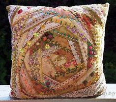 I love the use of fabric scraps and lace trimmings to create this pillow.The tiny pearls and hand embroidery complete this work of art!