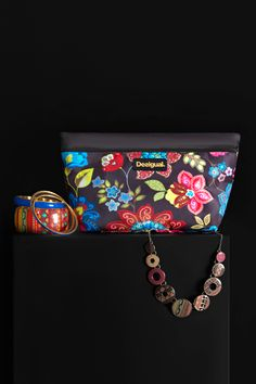 Desigual silver colorful necklace with interwoven pieces. Desigual set of bracelets. Desigual black toiletry bag with a contrasting floral print and a zipper fastening. This Autumn, renew your wardrobe enjoying our promos!