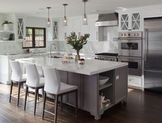 White and Gray Kitchen Inspiration. Large island with stools and lantern pendants hanging above. Stainless appliances and white countertops.