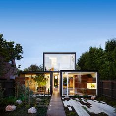 Casa moderna com as luzes acessas no final do dia.