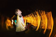 the ring bearer, celebrates at the wedding reception with bubbles with blurred light streaks in his super hero cape at their pema osel ling buddhist retreat center wedding in the santa cruz redwood mountains in corralitos, ca