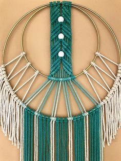 Dreamy handmade macrame wall hanging, made from hand dyed ombre teal cotton rope and a 12 brass ring. Features a modern design, wooden beads and fringe. Would make a lovely gift! Measures approx. 14 wide and 40 long. This piece is ONE OF A KIND and READY TO SHIP! ✦ Shop NEW Teal