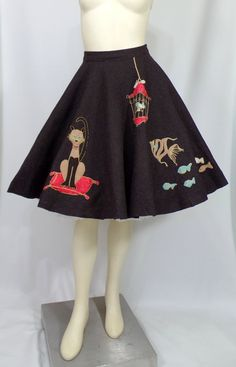 Novelty appliquéed wool felt circle skirt from the 1950s. Similar to a poodle skirt, this one features a Siamese cat, fish, a bird in a cage