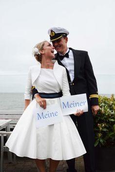 knielanges modernes rockabilly Hochzeitskleid im Marinelook mit Bolero passend zum Brautkleid mit Manschetten und Knöpfen  (http://www.noni-mode.de)