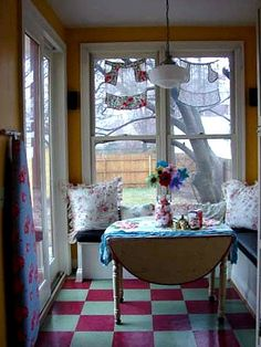 How cute! Look at the apron valances over those windows. Charming way to display grandmother's aprons!