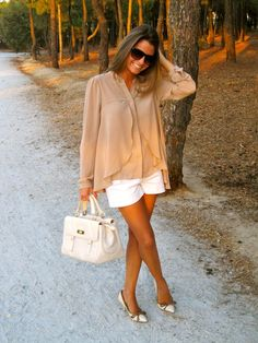 Nude hi-low top, white shorts, light cream bag and heels